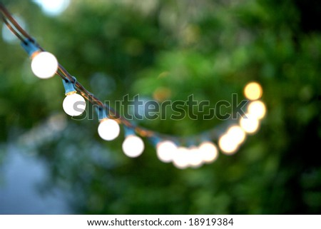 Hanging decorative christmas lights for a back yard party - stock photo