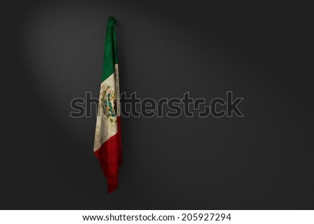 hanging dirty flag of mexico in the dark wall  - stock photo