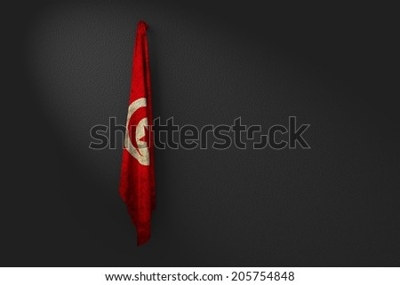 hanging dirty flag of tunisia in the dark wall