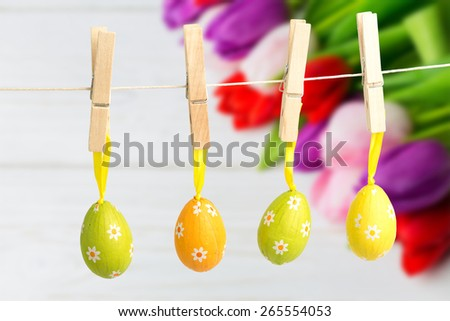 hanging easter eggs against tulips on table