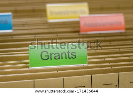 Hanging file folder labeled with Grants - stock photo