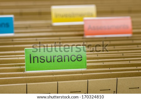 Hanging file folder labeled with Insurance - stock photo