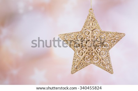 Hanging gold Christmas star with a colorful background - stock photo