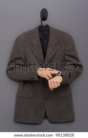 Hanging jacket with hands pointing out the time. - stock photo