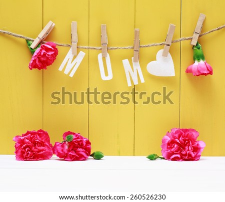 Hanging MOM letters with carnation flowers over yellow wooden wall - stock photo
