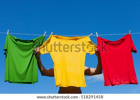 Hanging of wet shirts on clothesline.