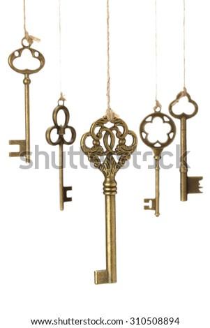 Hanging old Keys on white background. - stock photo