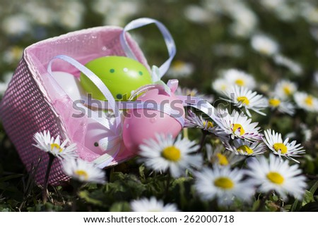 Hanging pink small basket with tiny bow a side carrying inside Easter eggs. Basket in outdoor field full of green grass with white flowers. - stock photo