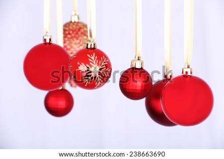 Hanging red Christmas balls on light background