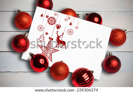 Hanging red christmas decorations against painted blue wooden planks - stock photo
