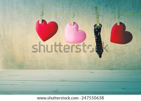 Hanging red pink hearts and condom still life art - stock photo