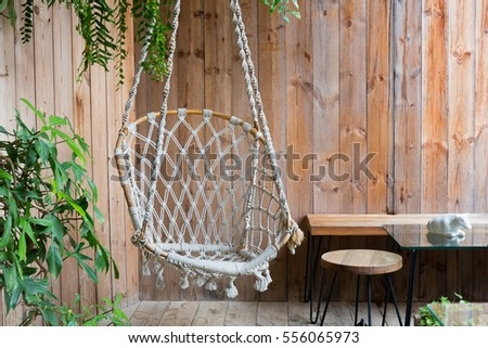Hanging Rope Chair In A Wooden Patio With Coffee Table And Green Plant.