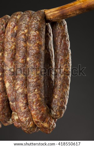 hanging smoked traditional sausage on a stick on black background