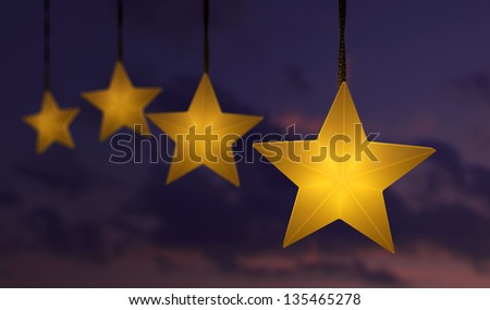 Hanging star shaped string lights over a dark sunset sky - stock photo