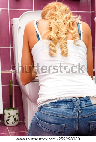 Hangover after a party, woman in the toilet - stock photo