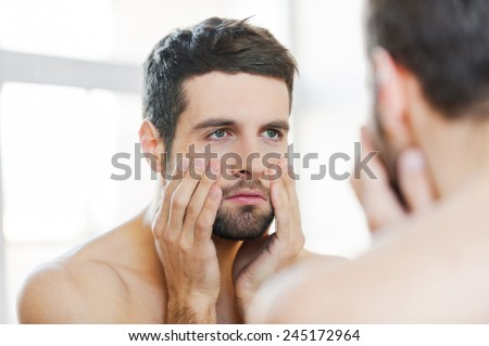 Hangover after night out. Frustrated young shirtless man touching his face and looking at himself while standing against a mirror  - stock photo