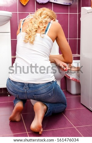 Hangover after party, woman in the toilet  - stock photo