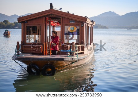 Hangzhou, China - December 5, 2014: Traditional Chinese wooden recreation boat goes on the West Lake, famous park in Hangzhou city - stock photo