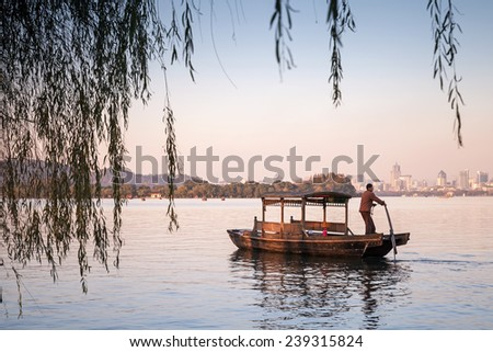 Hangzhou, China - December 5, 2014: Traditional Chinese wooden recreation boat with boatman floats on the West Lake. Famous park in Hangzhou city center, China - stock photo