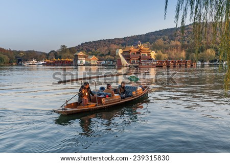 Hangzhou, China - December 5, 2014: Traditional Chinese wooden recreation boat with tourists and boatman floats on the West Lake. Famous park in Hangzhou city center, China - stock photo