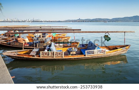 Hangzhou, China - December 5, 2014: Traditional Chinese wooden recreation boats floats moored on the West Lake, famous park in Hangzhou city - stock photo