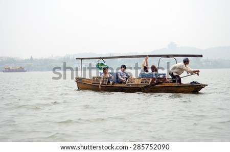 HANGZHOU, CHINA - MAY 3, 2015: Tourists enjoying a boat ride at the famous West Lake. It has influenced poets and painters throughout China's history for its natural beauty and historic relics. - stock photo