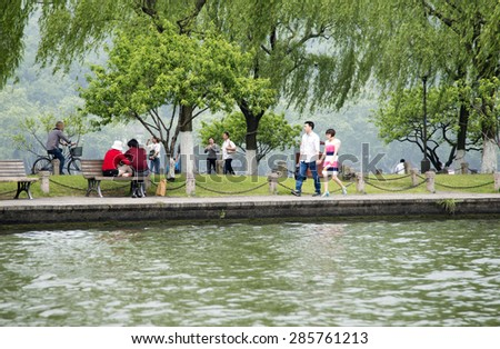 HANGZHOU, CHINA - MAY 3, 2015: Tourists enjoying by the Xihu (West Lake). West Lake has influenced poets and painters throughout China's history for its natural beauty and historic relics.