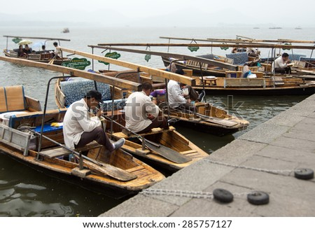 HANGZHOU, CHINA - MAY 3, 2015: Traditional Chinese wooden boats with boatmen on the Xihu (West Lake) taking a break and having some lunch. The lake has influenced poets and painters throughout China.