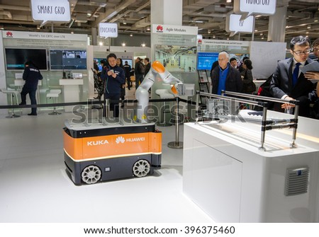 HANNOVER, GERMANY - MARCH 15, 2016: Industrial KUKA robot in booth of Huawei company at CeBIT information technology trade show in Hannover, Germany on March 15, 2016. - stock photo