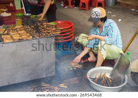 """Hanoi, Vietnam - Apr 5, 2015: A woman broil barbecue meat - the ingredient of """"bun cha"""" is the famous Vietnamese noodle soup with bbq meat, spring roll, vermicelli and fresh vegetable - stock photo"""