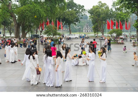 Hanoi, Vietnam - Apr 5, 2015: Group of students in Vietnamese traditional dress Ao Dai taking photos at Ly Thai To park, Dinh Tien Hoang street, by Hoan Kiem lake