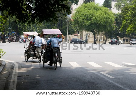 HANOI, VIETNAM, AUGUST 11: Cyclos drivers carry tourists on August 11, 2013 in Hanoi, Vietnam. Cyclo used to be a popular transportation in Vietnam, it is for tourism now