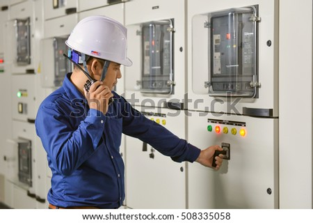 Hanoi, Vietnam 06 August 2016: Hawee worker operating Main electric switchboard at site with phone, talkie. Blokset Schneider, fully type test, standard IEC switchboard
