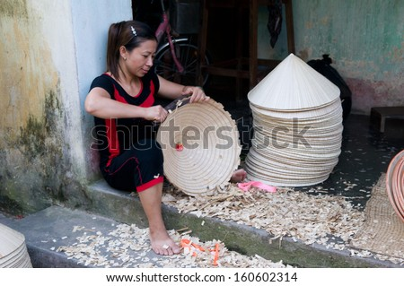 HANOI, VIETNAM, AUGUST 12: Unidentified woman makes conical hat on August 12, 2013 in Hanoi, Vietnam. Making conical hat is a traditional handicraft job in Chuong village, Thanh Oai district, Hanoi