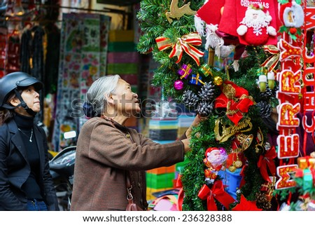 Hanoi, Vietnam - Dec 7, 2014: An old woman picks Christmas decorations for buyer in store on Hang Ma street, quarter of Hanoi. The business starts late November until Christmas day every year - stock photo
