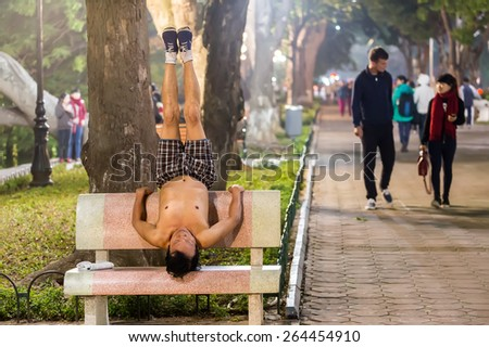 HANOI, VIETNAM, DECEMBER 15, 2014: A man is practicing Yoga on a public bench in evening at the city center's Hoan Kiem lake in Hanoi city, Vietnam. - stock photo