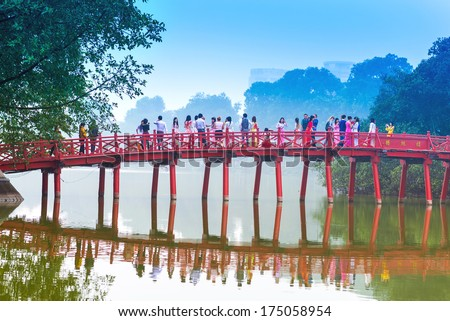 HANOI,VIETNAM - DECEMBER 01: Huc Bridge over the Hoan Kiem Lake on December 01, 2012 in Hanoi,Vietnam.The wooden red-painted bridge connects the shore and the Jade Island on which Ngoc Son Temple - stock photo