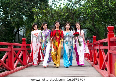 HANOI, VIETNAM, DECEMBER 20: Vietnamese girls with Ao Dai on The Huc bridge on December 20, 2012 in Hanoi, Vietnam. Ao dai is famous traditional custume for woman in VIetnam.