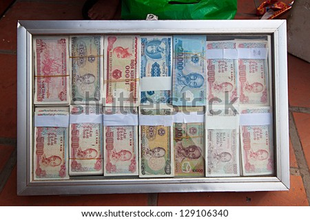 HANOI, VIETNAM FEB 13: Carrying new money in Hanoi Vietnam February 13, 2013. New currency exchange Vietnamese people in the new year for good luck, this is the traditional custom of Vietnam. - stock photo