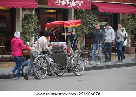 Hanoi, Vietnam,February 3 : An unidentified tourist sits in traditional cycle vehicle in the busy Hanoi traffic on February 3, 2015