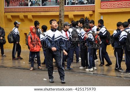 HANOI, VIETNAM - FEBRUARY 19, 2013: Children in Vietnamese uniform playing in the front of their school in Hanoi - stock photo