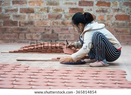 Hanoi, Vietnam - Jan 1, 2016: Asian female crafswoman processing ceramic brick after drying under the sunlight at Kim Lan traditional village, on the other river bank of Bat Trang village in Hanoi. - stock photo