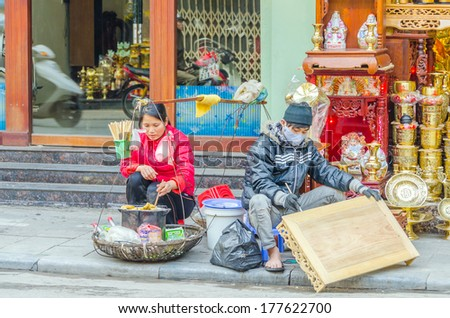 HANOI, VIETNAM, JANUARY 13, 2013 - an artisan is painting a carved table sitting on street while a woman is cooking some food for sale