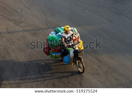 Hanoi, Vietnam - July 23, 2016: Aerial view of Vietnamese woman transporting fruit by motorcycle on Yen Phu street in early morning