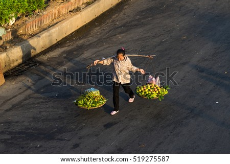 Hanoi, Vietnam - July 23, 2016: Aerial view of Vietnamese woman vendor carrying fruit on balance on Yen Phu street in early morning