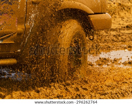 Hanoi, Vietnam: July 4, 2015: Color detail shot of an off-road car's wheel, covered in mud, Mitsubishi Triton car. - stock photo