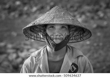 Hanoi, Vietnam - June 12, 2016: Black and white portrait of woman farmer wearing conical hat in Son Tay provincial town
