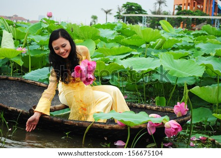 HANOI, VIETNAM, JUNE 12: Unidentified Vietnamese girl wear Ao dai and sit on boat in lake of lotus on June 12, 2010 in Hanoi, Vietnam. Ao dai is famous traditional custume for woman in VIetnam.