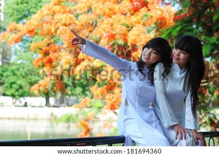 HANOI, VIETNAM, JUNE 12: unidentified Vietnamese girls wear Ao dai near flamboyant tree on June 12, 2011 in Hanoi, Vietnam. Ao dai is famous traditional custume for woman in VIetnam.