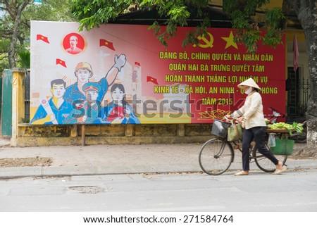 Hanoi, Vietnam - Mar 29, 2015: A vendor walking pass a communist propaganda in To Hien Thanh street - stock photo